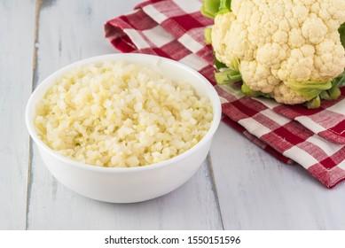 Close up of mane ingredient for cauliflower fried rice - bowl with cauliflower rice.