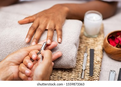 Close up of manicurist hands clipping client nails in a luxury spa. Young woman getting manicure treatment with hands kept on towel. Clipping nails, hand care and nailcare at beauty salon. - Shutterstock ID 1559873363