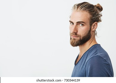 Close up of manly handsome guy with fashionable hairstyle and beard looking in camera, holding head in three quarters with serious expression.