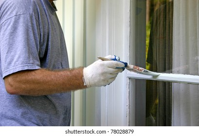 Close up of a man's arm and hand carefully painting the edge of an exterior house window
