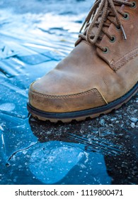 Close up of man's boots step on icy surface of ground.