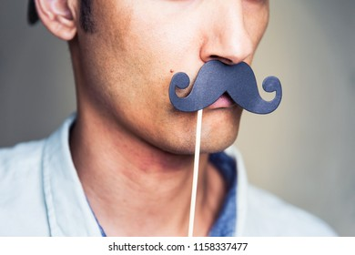 close up of a man's chin wearing a fake paper made mustache