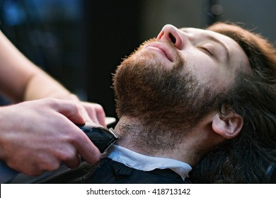 Close up man's face at the barbershop - barber's hands are shaving his beard with a machine