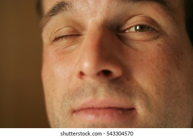 Close up of a man's face winking with the right eye