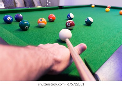 Close up of a man's hand and arm playing pool preparing to shoot the white ball of a Black and green Pool / Billiard / Snooker Table with a complete set of pool balls, and the white ball