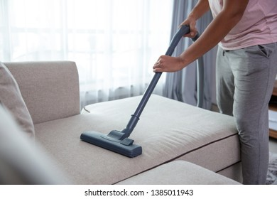 close up of man's hand cleaning couch using vacuum cleaner at home