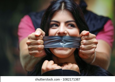 Close up of a mans hand covering a womans mouth with tape. Concept of domestic violence or kidnapping