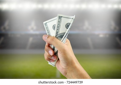 Close up of a man's hand crushing a wad of hundred dollar bills in concept of getting money with bets in soccer