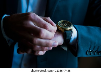 Close up of man's hand fastening a cuff before getting married. Wedding detail Man puts blue cufflink on his white sleeve Elegant man adjusting his watch Man in a white shirt adjusts his wristwatch.
