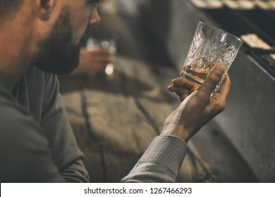 Close up of man's hand holding crystal glass of whiskey or brandy. Bearded man drinking and tasting strong drinks and elite alcohol in bar. Concept of expensive alcoholic beverages.