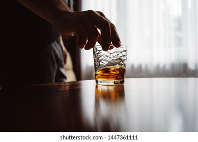 Close up of man's hand holding glass of whiskey. Tasting and degustation concept. Businessman in elegant suit with glass of whiskey. Place for text