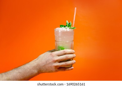 Close up of a man's hand holding a glass of tropical mojito cocktail on orange background with copy space. Summer time vacation concept.