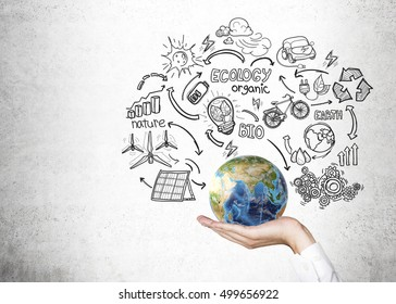 Close up of man's hand holding globe surrounded by sketches of renewable energy sources on concrete wall. Concept of being responsible. Mock up. Elements of this image furnished by NASA