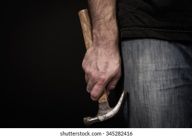 Close up of a man's hand holding a hammer at his side wearing blue jeans