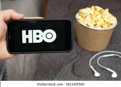 Close up mans hand holding a mobile phone with HBO logo with Apple earphones and popcorn box next to him, August 2020, San Francisco, USA