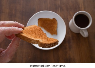 Close up of a man's hand holding toast over plate from a unique point of view. Shallow depth of field with focus on toast in hand.