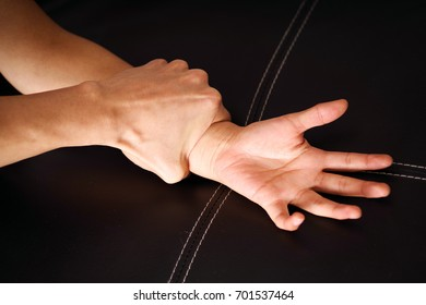 Close up man's hand holding a woman wrist over a black coach for rape and sexual abuse concept