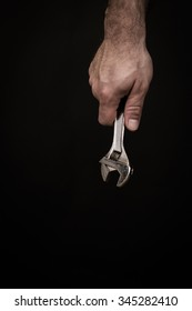 Close up of a man's hand holding a wrench in front of a black background