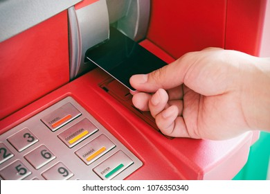 Close up of man's hand insert ATM card into Automated teller machine (Automatic banking machine) to withdraw cash money, Banking and Business Concept.