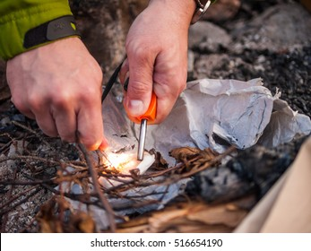Close up of a man's hand lighting fire with a fire-steel at outdoors.