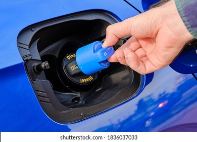 Close up mans hand opening a tank for Ad Blue fluid of a blue car. Diesel exhaust fluid or DEF for reduction of air pollution, October 2020, Prague, Czech Republic