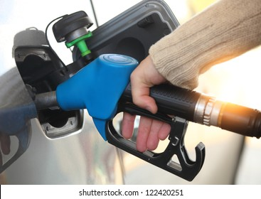 Close up of a mans hand refilling the car with a gas pump