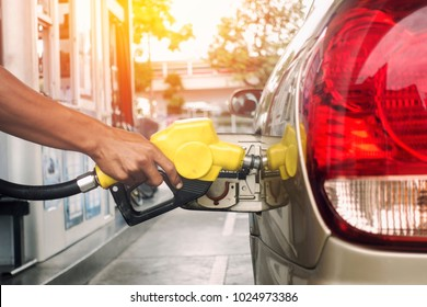 Close up man's hand is refuelling. in the refuelling station to travel