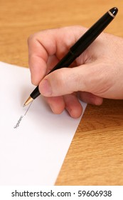 A close up of man's hand signing a contract
