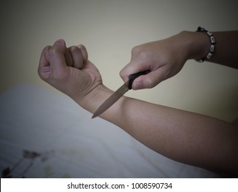 Close up of a man's hand slitting wrist on the bed