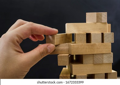Close up of man's hand take one block to a tower of wooden blocks, dark tone.