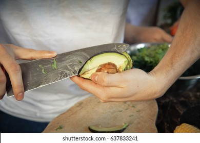 Close up man's hands cutting and peeling avocado.Safety precautions. The knife is in a dangerous position, the probability of injuring a hand.accident prevention