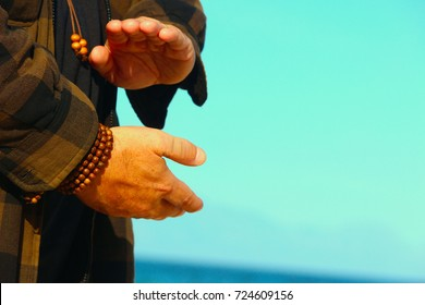 close up of a man's hands  doing Qigong routine, holding a ball of chi