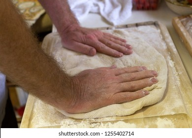 Close up of a man's hands kneading dough on a cutting board to make fresh bread