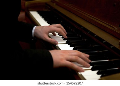 Close up of a man's hands playing a piano