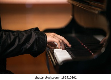 Close up of a man's hands playing a piano in church.