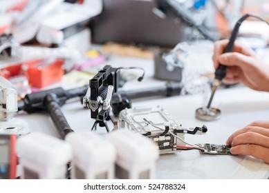 Close up of mans hands soldering drone mechanism