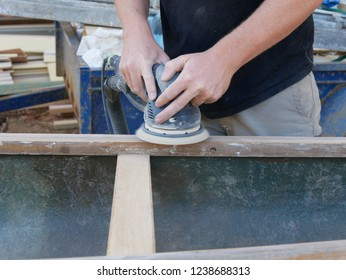 Close up of a man's hands and torso using a power tool to sand the hardwood on a vintage fiber glass canoe restoration project with a worksite trailer and timber pile in the background in Australia