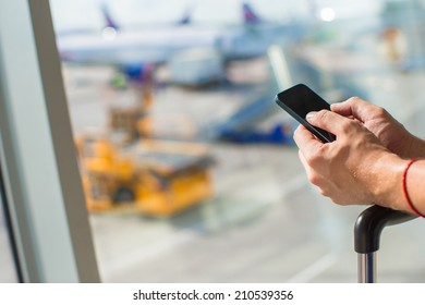 Close up man's hands using cellphone inside airport
