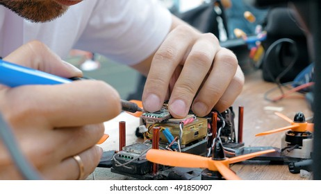 Close up of man's hands welding details while assembling FPV drone using tools, preparing quadcopter for flight. Repair drone before training process.