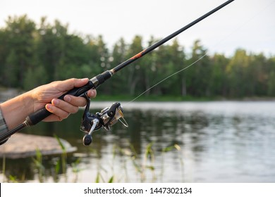 Close up of a man's left hand holding a fishing rod. Sunset soft light, selective focus, blurred forest and lake in the background. Vacation, camping, fishing, relaxing and hobby concept.
