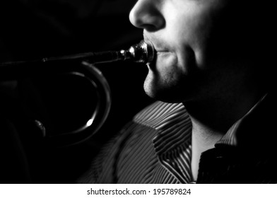 Close up of a man's lips and cheeks while playing a trumpet