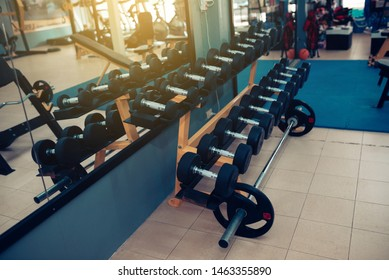 Close up many black dumbbells set on the rack in sport fitness center with the backdrop of the sun or sun light.