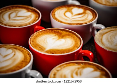Close up of many cups of cappuccino with latte art on dark background