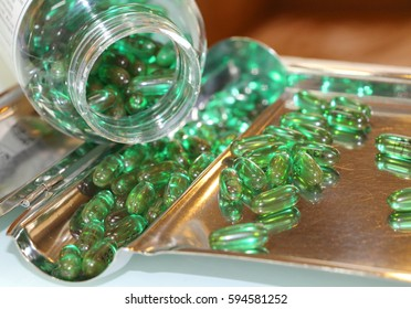 Close up of many green capsules on the stainless tray.  Many green capsules of pain killer at drug store. A pharmacist is counting the medicine.