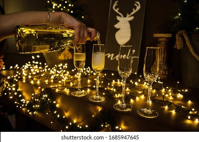Close up of many hand pour champagne or wine in the glasses with christmas dark light background