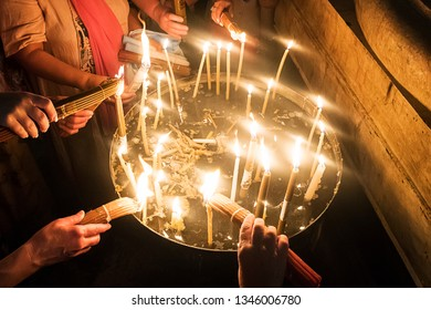 Close up of many hands burning candles after the Holy Fire miraculously appeared at Temple of the Lord's Coffin, Jerusalem, Israel. Pilgrims taking holy fire after ritual symbolising Resurrection