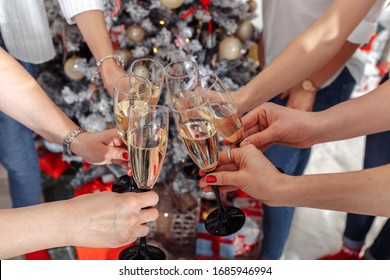 Close up of many hands holding glasses of champagne/ wine with christmas tree in the background