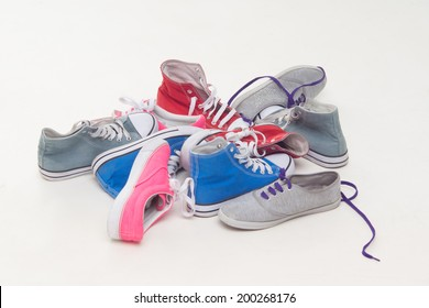 Close up of many lace-up shoes and sneakers isolated on white background. Concept of shopping, style, fashion