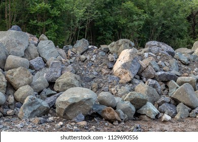 Close up many large piles of granite rocks on the ground near the forest with early morning light.
