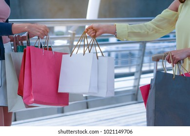 Close up of many shopping bags that were holding by couple girls or hand of woman in summer sale